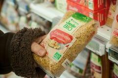 Nahaufnahme von natürlichen Teigwaren in der Hand bei Cora Supermarket lizenzfreie stockbilder