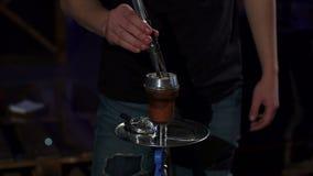 Nahaufnahme von ?nderungen eines Mannes eine gebrannte Kohle in einer Huka in einer dunklen Hukastange stock video