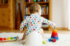 Nahaufnahme von netten kleinen 12 Monate alten Kleinkindbaby-Kind, die auf Töpfchen sitzen Lizenzfreies Stockbild