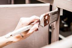 Nahaufnahme von Person Painting Kitchen Cabinets Stockbild