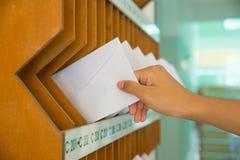 Nahaufnahme von Person ` s Hand, die Buchstaben vom Briefkasten entfernt Stockfoto
