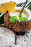 Nahaufnahme von pinacolada in der Kokosnuss auf Strand Stockbild