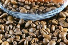 Nahaufnahme von Röstkaffeebohnen und von Glas/Glasschale ist folgend lizenzfreie stockfotos