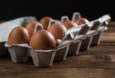 Nahaufnahme von rohen Hühnereien in einem Kasten Eier auf einem alten Holztisch Stockbild