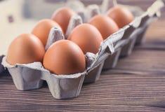 Nahaufnahme von rohen Hühnereien in einem Kasten Eier auf einem alten Holztisch Lizenzfreie Stockbilder