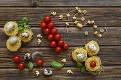 Nahaufnahme von rohen traditionellen italienischen Teigwaren mit Kirschtomaten Lizenzfreie Stockbilder