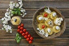 Nahaufnahme von rohen traditionellen italienischen Teigwaren mit Kirschtomaten Stockfotos
