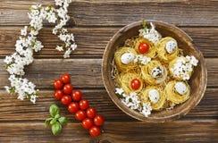 Nahaufnahme von rohen traditionellen italienischen Teigwaren mit Kirschtomaten Stockfotografie