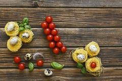Nahaufnahme von rohen traditionellen italienischen Teigwaren mit Kirschtomaten Lizenzfreie Stockfotografie