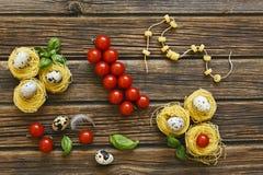 Nahaufnahme von rohen traditionellen italienischen Teigwaren mit Kirschtomaten Stockbild
