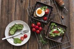 Nahaufnahme von roten Kirschtomaten mit frischem Frühstück auf Platten Stockbild