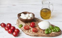 Nahaufnahme von roten Kirschtomaten mit weißem Mozzarellakäse, Olivenöl und grünen Blättern des Basilikums auf weißem hölzernem H Lizenzfreies Stockbild