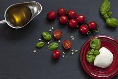 Nahaufnahme von roten Kirschtomaten mit weißem Mozzarellakäse, Olivenöl und grünen Blättern des Basilikums auf schwarzem Hintergr Lizenzfreies Stockfoto