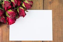 Nahaufnahme von roten Rosen auf einem hölzernen Hintergrund mit leerem Mitteilungs-Zeichen für Ihren Text oder Mitteilung Lizenzfreie Stockfotos