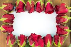 Nahaufnahme von roten Rosen auf einem hölzernen Hintergrund mit leerem Mitteilungs-Zeichen für Ihren Text oder Mitteilung Grußkar Stockfotos