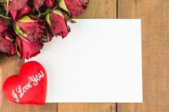 Nahaufnahme von roten Rosen und rotes Herz auf einem hölzernen Hintergrund mit leerer Mitteilung unterzeichnen für Ihren Text ode Lizenzfreie Stockfotos