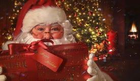Nahaufnahme von Sankt Geschenk mit Weihnachtsszene im Hintergrund halten Lizenzfreie Stockfotos