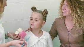 Nahaufnahme von schönen Mädchen und von ihrer Mutter Sie sitzen im Zahnarzt sind Büro Kinder ist Doktor spricht über das mögliche stock footage