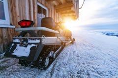 Nahaufnahme von Schneemobil fahrung Parken nahe bei Blockhaus Lizenzfreie Stockfotografie