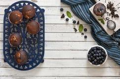 Nahaufnahme von Schokoladenkleinen kuchen mit Blaubeeren auf weißer Schüssel auf hölzernem Hintergrund Lizenzfreie Stockfotos