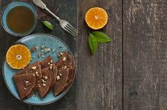 Nahaufnahme von Schokoladenpfannkuchen mit Orangen auf blauer Platte Stockfotos