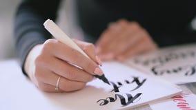 Nahaufnahme von Schreibkünstlerhänden schreibt Phrase auf Weißbuch Einschreiben von dekorativen verzierten Buchstaben kalligraphi stock video