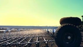 Nahaufnahme von Seite zu Landwirt, Traktor auf Pflügen der großen Räder, eggt Boden mit großem Metallpflug, anhebt Los Staub  stock video