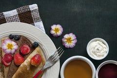 Nahaufnahme von selbst gemachten Pfannkuchen mit Erdbeeren auf weißer Platte mit Tasse Tee auf Tabelle mit Weinlesegabel Lizenzfreie Stockfotografie