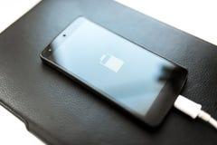 Nahaufnahme von Smartphone mit Symbol der schwachen Batterie Stockfotografie