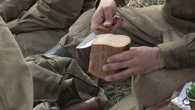 Nahaufnahme von Soldaten in einer russischen Militäruniform vom zweiten Weltkrieg schneidet Brot mit einem Messer stock video footage