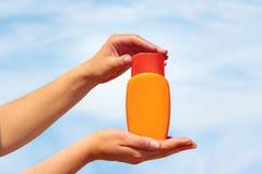 Nahaufnahme von sunblock in den weiblichen Händen auf Strand Stockbild