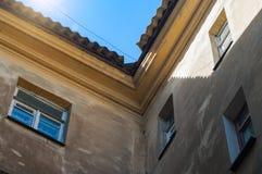 Nahaufnahme von Wänden mit Windows und von Dach eines düsteren alten Wohnhauses Stockbild