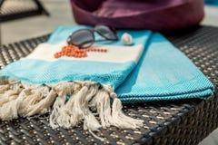 Nahaufnahme von Weiß und von türkischem Tuch des Türkises, von Sonnenbrille, von orange Halskette und von Strohhut auf Rattanruhe Lizenzfreies Stockbild