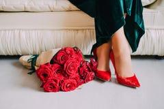 Nahaufnahme von weiblichen Füßen in den roten Samtschuhen mit roten Rosen Stockbild