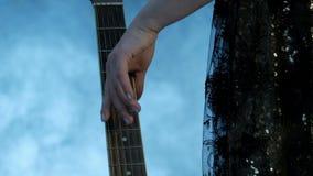 Nahaufnahme von weiblichen Fingern Ein Mädchen in einem Konzertkleid nähert sich dem Gitarrenhals und führt sie leicht, die Schnü stock footage