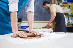 Nahaufnahme von weiblichen Händen beim Vorbereiten von Clay Pieces auf Tabelle in der Werkstatt Stockfoto