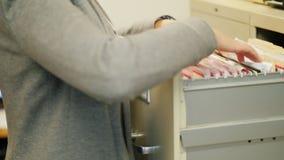 Nahaufnahme von weiblichen Händen nehmen einen Ordner mit Dokumenten von einem Fach im Retrostil Archivierte Arbeit stock footage