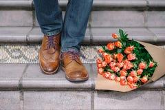 Nahaufnahme von Weinleseschuhen mit purpurroten Spitzeen und ein Blumenstrauß von ROS Lizenzfreie Stockfotografie