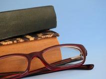 Nahaufnahme von zwei alten Büchern und von Brillen auf einem blauen Hintergrund stockfotografie