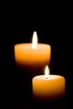 Nahaufnahme von zwei beleuchtete Kerzen auf schwarzem Hintergrund. Stockbild