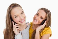 Nahaufnahme von zwei jungen Frauen, die am Telefon lächeln Stockbild