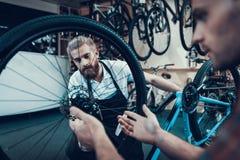 Nahaufnahme von zwei Kerlen reparieren Fahrrad in der Sport-Werkstatt lizenzfreies stockfoto