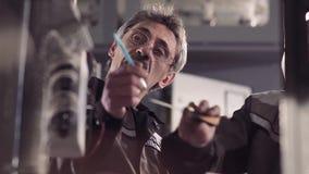 Nahaufnahme von zwei Mitarbeitern, die Arbeit an einer Fabrik besprechen stock footage