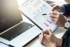 Nahaufnahme von zwei Wirtschaftlern, die Diagramm im Büro besprechen Stockbild