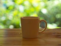 Nahaufnahme weiße Cofee-Schale auf dem Holztisch mit einem grünen Blatt bokeh stockbild