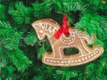 Nahaufnahme-Weichzeichnungspferdelebkuchen auf Weihnachtsbaum verzieren ChristmasDay-Hintergrund lizenzfreie stockfotografie