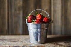 Nahaufnahme wenigen Eimers mit den frischen und saftigen Erdbeeren auf hölzernem Hintergrund der Weinlese Stockbild