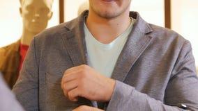 Nahaufnahme-Zeitlupe-junger gutaussehender Mann versucht an Grey Jacket stock video footage