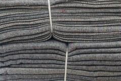 Nahaufnahme zum Stapel Gray Blankets Tied With White-Plastikseil-Hintergrund Stockfotos