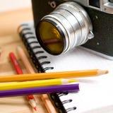 Nahaufnahme-Zusammensetzung mit Mechaniker photocamera, Bleistiften und einem Notizbuch Lizenzfreie Stockbilder
